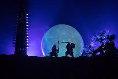 Samoeraien het vechten concept Silhouet van samurais in duel dichtbij boom en oude tempel Beeld met twee samurais en zonsondergan royalty-vrije stock foto