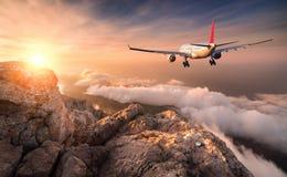 Samolot lata nad chmurami przy zmierzchem Obrazy Royalty Free