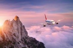 Samolot lata nad chmurami przy zmierzchem Krajobraz Obrazy Royalty Free