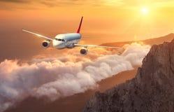 Samolot lata nad chmurami przy zmierzchem Krajobraz Zdjęcie Stock