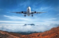 Samolot lata nad niskimi chmurami i górami Zdjęcia Stock
