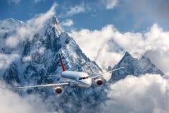 Samolot lata nad niskimi chmurami przeciw górom Zdjęcie Royalty Free