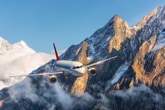 Samolot lata nad niskimi chmurami przeciw górom Obrazy Stock