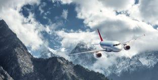 Samolot lata nad niskimi chmurami przeciw górom Obraz Royalty Free
