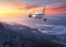 Samolot lata nad niskimi chmurami przy zmierzchem Zdjęcie Stock