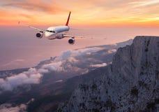 Samolot lata nad skałami i chmurnieje przy zmierzchem Obraz Stock