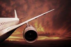 Samolot lata przy zmierzchem zdjęcie stock