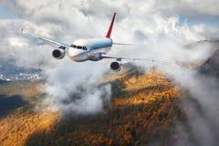 Samolot lata w chmurach nad górami z jesień lasem Zdjęcia Stock