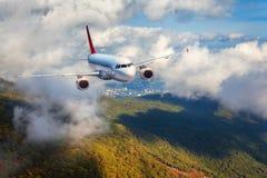 Samolot lata w chmurach nad górami z lasem przy sunse Zdjęcie Royalty Free