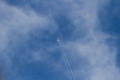Samolot między chmurami opuszcza ślad w niebie Zdjęcie Royalty Free