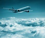 Samolot pasażerski lata nad cumulus chmurami Zdjęcia Royalty Free