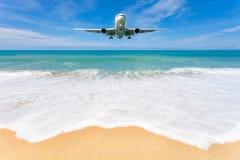 Samolotowy lądowanie nad piękny plaży i morza tło Obrazy Royalty Free