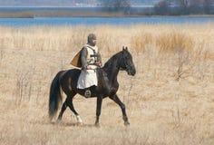 Adeln Sie in einer Rüstung rittlings auf einem Pferd Stockfotografie
