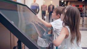 Samoobsługa przy centrum handlowym, nowożytną dziecko chłopiec i dziewczyną, używa Ewidencyjnego orientowanie system Dla rewizi l zbiory