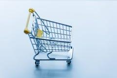 Samoobsługowy supermarket robi zakupy małą tramwaj furę na białym b Obraz Stock