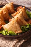 Samosa with lettuce on a wooden table. Vertical closeup Stock Photo