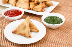 Samosa with Mint Chutney. Closeup view of delicious deep fried south Indian samosa with mint chutney and tomato sauce Royalty Free Stock Image