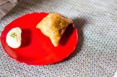 Samosa, peda barfi auf roter Platte und gesponnener Matte, typisches indisches Imbissfrühstück lizenzfreie stockfotografie