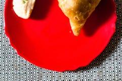 Samosa, peda barfi auf roter Platte und gesponnener Matte, typisches indisches Imbissfrühstück stockfoto