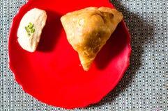 Samosa, peda barfi auf roter Platte und gesponnener Matte, typisches indisches Imbissfrühstück stockfotografie
