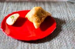 Samosa, peda barfi auf roter Platte und gesponnener Matte, typisches indisches Imbissfrühstück lizenzfreie stockfotos