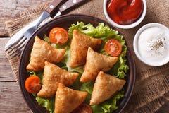 Samosa on a plate with sauce closeup, horizontal top view Stock Image