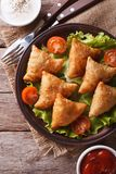 Samosa on a plate with sauce closeup, vertical top view Royalty Free Stock Photos
