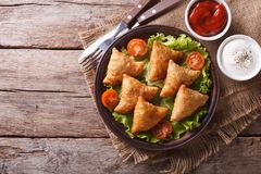 Samosa on a plate with sauce, horizontal top view