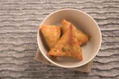 Samosas在一个白色碗的一个被油炸的三角酥皮点心小包或肉的包裹的辣混合菜 免版税图库摄影