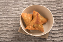 Samosas a spicy blend of vegetables or meat wrapped in a deep fried triangular pastry parcel in a white bowl Stock Photos