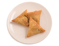 Samosas a spicy blend of vegetables or meat wrapped in a deep fried triangular pastry parcel in a white plate Stock Photography