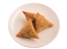 Samosas a spicy blend of vegetables or meat wrapped in a deep fried triangular pastry parcel in a white plate. Stock Images