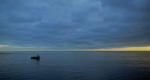 Samotna łódź cumuje na płaskim morzu przy wschód słońca zdjęcie stock