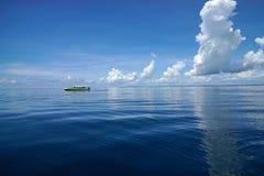 Samotna łódź przy otwartym morzem z niebieskim niebem Obrazy Royalty Free