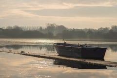 Samotna bezpilotowa łódź siedzi bezczynnie na zamarzniętym jeziorze podczas wschód słońca na Hornsea Zwyczajnym fotografia royalty free
