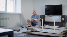 Samotna istota ludzka gromadzić nowego meble, instaluje części i załatwia je w lekkim pokoju, dom, szczegóły i narzędzia, zdjęcie wideo