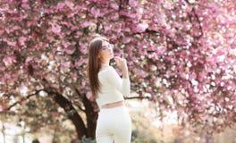 Samotna piękna dziewczyna z romantyczną fryzurą i fachowym makijażem cieszy się odór różowi kolory w ogródzie _ fotografia royalty free