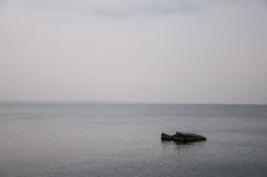 samotna skała po środku szarego morza Obrazy Royalty Free
