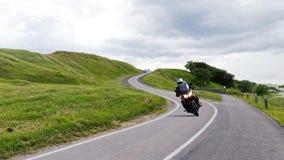 Samotne motocyklista przejażdżki wzdłuż wąskiej drogi zdjęcie stock