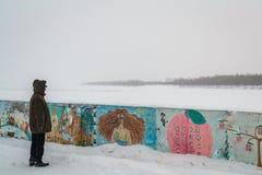 Samotni mężczyzna spojrzenia przy wodną zimą obrazy stock