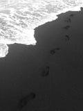 Samotni odciski stopy po tym jak spacer dalej na czarnej piasek plaży oceanem - Maui, Hawaje Fotografia Royalty Free