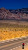 Samotny cyklista przy rewolucjonistki skałą Caynon, Nevada Zdjęcie Royalty Free