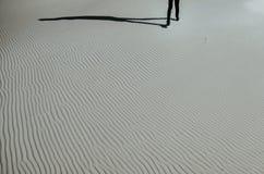 Samotny mężczyzna chodzi białego piasek Fotografia Stock
