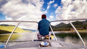 Samotny młody człowiek relaksuje być usytuowanym na łódkowatym główkowaniu i koncentrować zdjęcia royalty free