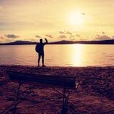 Samotny podróżnik z plecakiem Mężczyzna na morze plaży przy drewnianą ławką, zimny pogodny jesień wieczór Fotografia Royalty Free