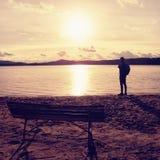 Samotny podróżnik z plecakiem Mężczyzna na morze plaży przy drewnianą ławką, zimny pogodny jesień wieczór Zdjęcie Royalty Free
