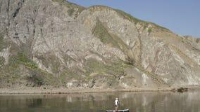 Samotny sup surfingowiec rusza się wzdłuż spokojnej błękitne wody wzdłuż halnego skalistego brzeg antena zdjęcie wideo