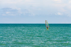 Samotny surfingowiec w na pokładzie morza z jasnym niebieskim niebem Obraz Stock