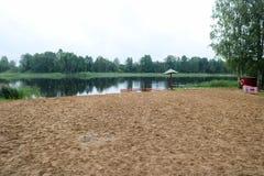 Samotny, zwisający zapadnięty parasol, i fechtunek, kojec dla kąpać się dzieci na piaskowatej plaży na brzeg jezioro, rzeka przy  obrazy stock