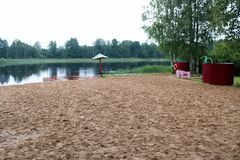 Samotny, zwisający zapadnięty parasol, i fechtunek, kojec dla kąpać się dzieci na piaskowatej plaży na brzeg jezioro, rzeka przy  obrazy royalty free